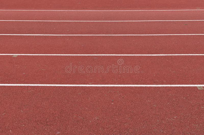 Horizontal red running track cross section. Horizontal  cross section view of a red surface running track with white lines to mark the lanes royalty free stock images