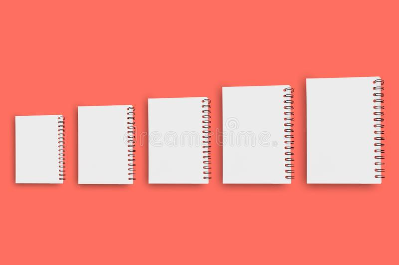 Horizontal row of five blank paper notepads with spiral wire for note or drawing from small to large on background of living coral stock photo
