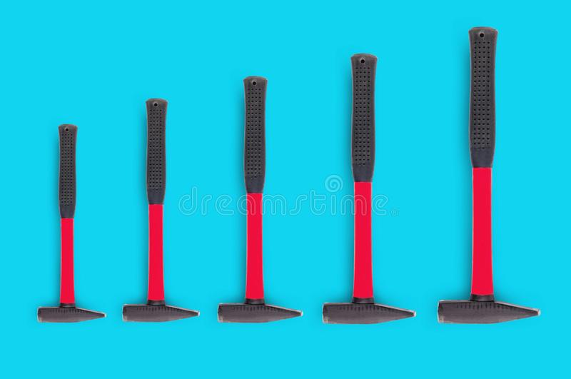 Horizontal row of five metal hammers with red and black rubber handle from small to large. On blue background stock photography