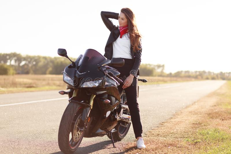 Horizontal shot of active female motorcyclist pose on fast bike in open air, wears red bandana, black leather jacket and sneakers. Focused aside, takes break stock photography