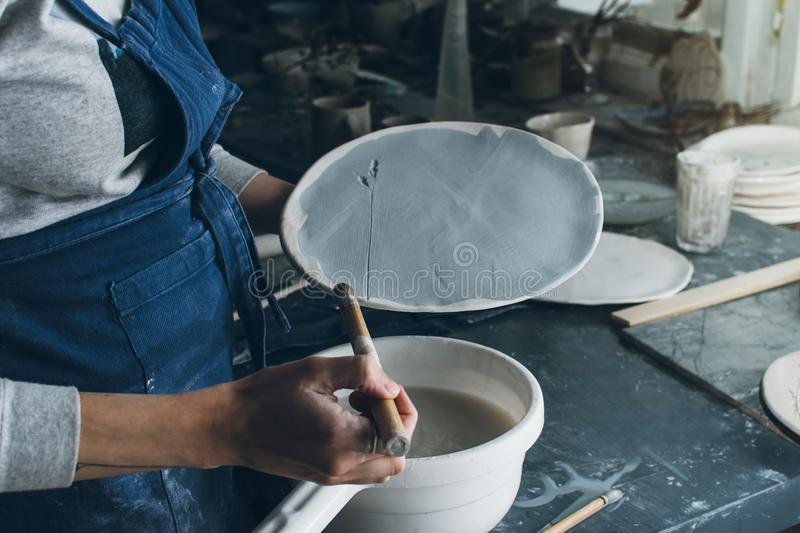 Horizontal shot of artist woman holding a clay dish stock image