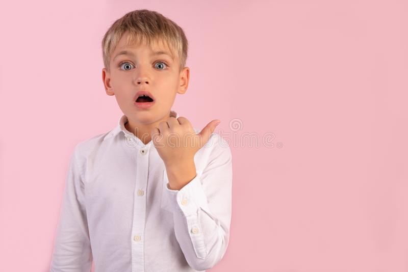 Horizontal shot of attractive amazed European male chiled in fashionable shirt points aside with thumb, shows something against royalty free stock photos