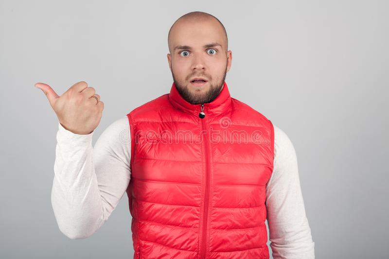 Horizontal shot of attractive amazed unshaven European male in red waistcoat points aside with thumb, shows something against royalty free stock photography