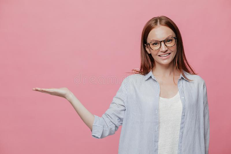 Horizontal shot of attractive young lady holds free space, dressed in formal clothes, smiles gently, poses over pink background, royalty free stock images