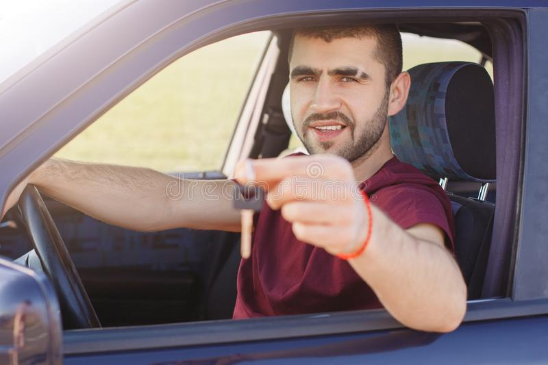Horizontal shot of attractive young male driver poses in car, shows keys, sells his automobile, covers long destination, has dark stock images