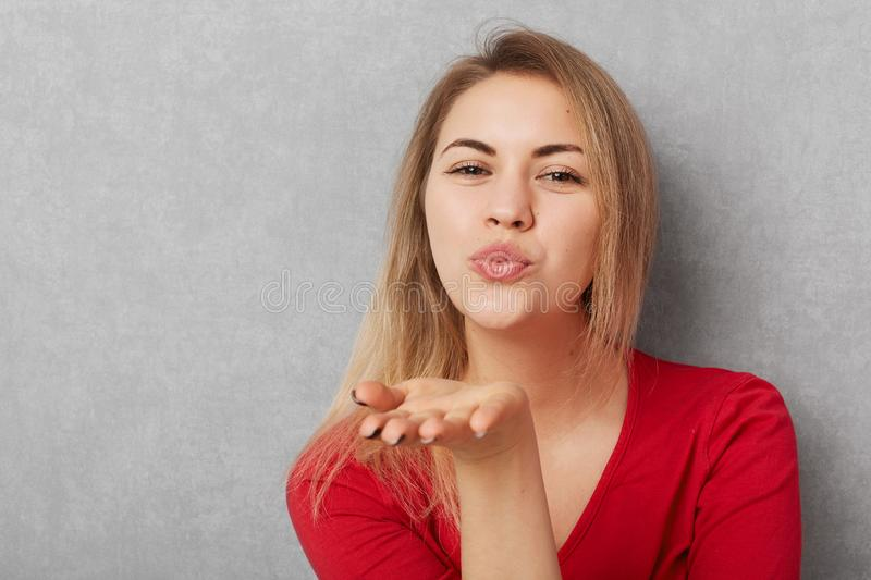 Horizontal shot of beautiful young woman with appealing appearance, makes air kiss, blows at camera, wears red sweater, o royalty free stock photography