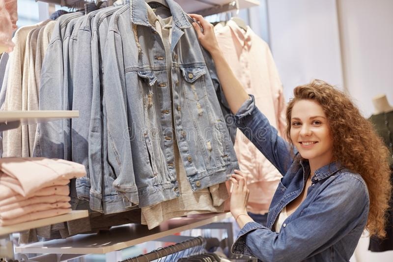 Horizontal shot of beautiful young woman with curly hair, pleased expression, chooses new denim jacket in clothing store, has sati royalty free stock image