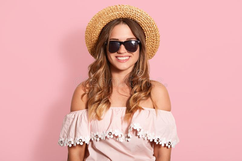 Horizontal shot of beautiful young woman in summer shirt with bare shoulders and sun hat, looking smiling at camera, has happy royalty free stock photography