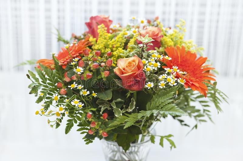 Bouquet of orange, yellow and red flowers in a vase on white background. royalty free stock photography