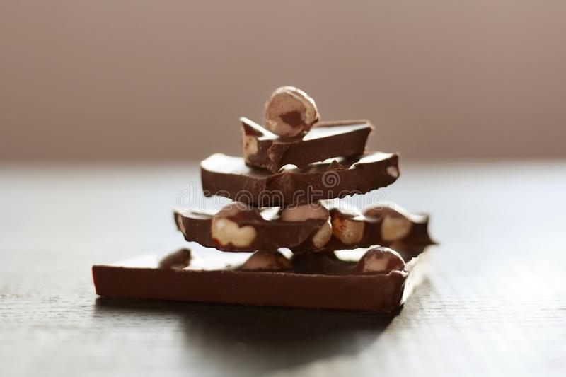 Horizontal shot of brown table with chocolate, handmade pyramide from chocholate pieces isolated over dark surface, milk. Chocholate with nuts lying on brown royalty free stock photo