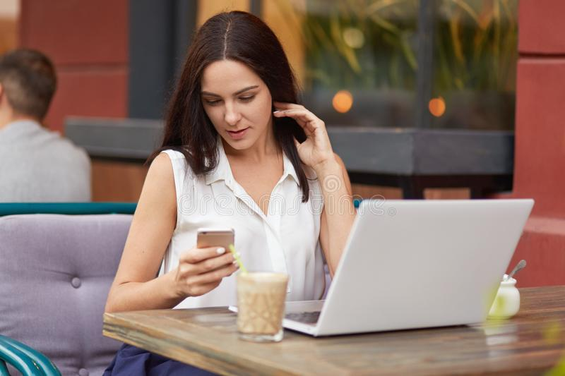 Horizontal shot of busy female freelancer holds mobile phone, text messages online, uses laptop computer, drinks milkshake, poses royalty free stock images