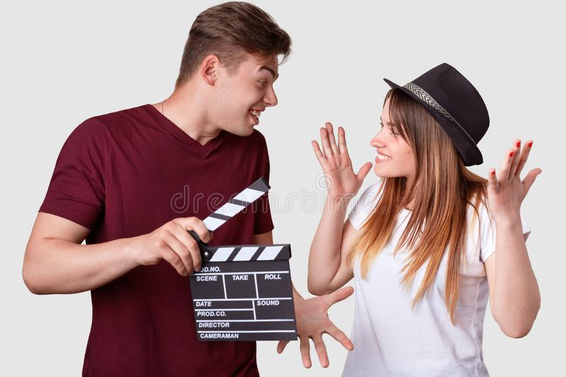 Horizontal shot of cheerful woman and man look positively at each other, gesture actively, have hesitant expressions, holds. Horizontal shot of cheerful women stock images