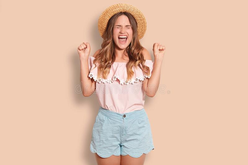 Horizontal shot of cheerful young European female clenches fists, exclaims with happiness, closes eyes, wears summer hat, blouse a. Nd shorts, poses against stock photo