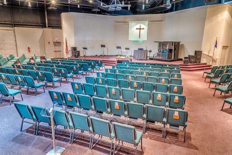 Empty Church Sanctuary. Horizontal shot of a church auditorium from the back facing toward the stage looking from the right side of the sanctuary stock photo
