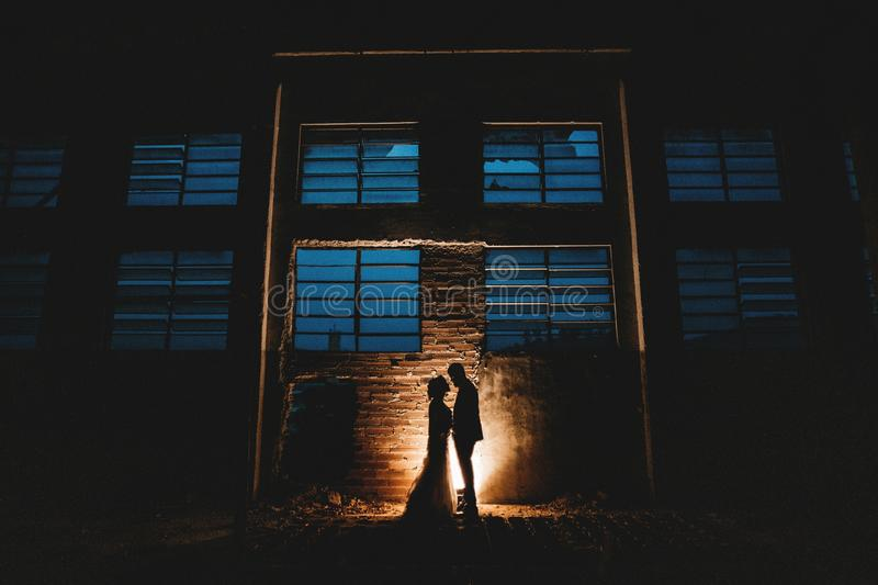 Horizontal shot of a couple` standing near a light source in silhouette in an abandoned building. A horizontal shot of a couple` standing near a light source in royalty free stock image