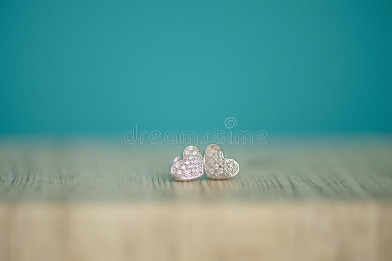 Heart shaped silver pair of earrings with genuine or faux diamonds stock photography