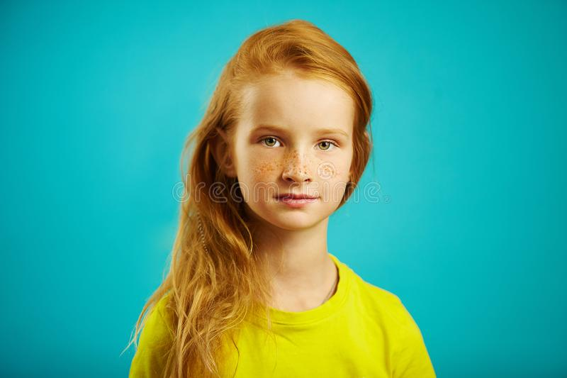 Horizontal shot of cute children girl with sincere look of kindness and honesty, has red hair, beautiful freckles, wears royalty free stock photography