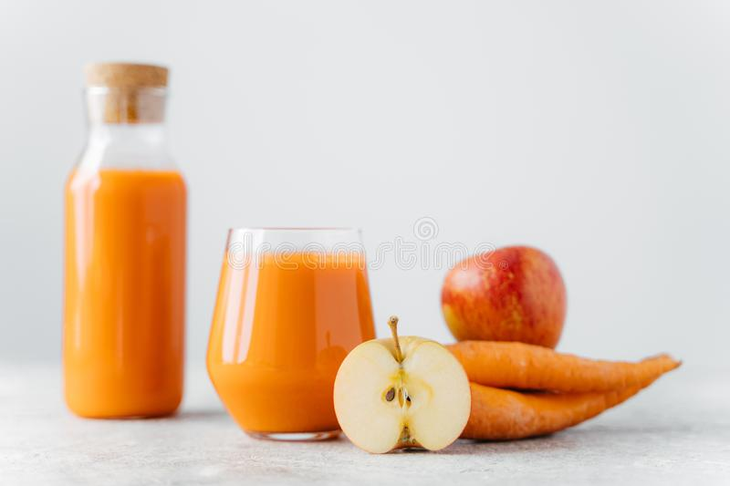 Horizontal shot of detox carrot juice in bottle and glass, slice of apple, carrot,  over white background. Healthy natural royalty free stock photos