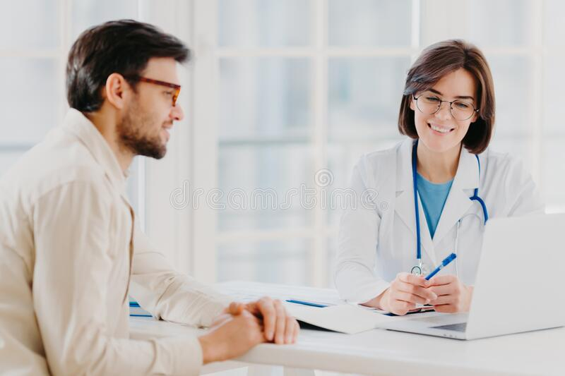Horizontal shot of doctor and patient discuss something, talk about diagnosis, use laptop computer, pose in consulting room, check. Medical records. Sick men royalty free stock photos