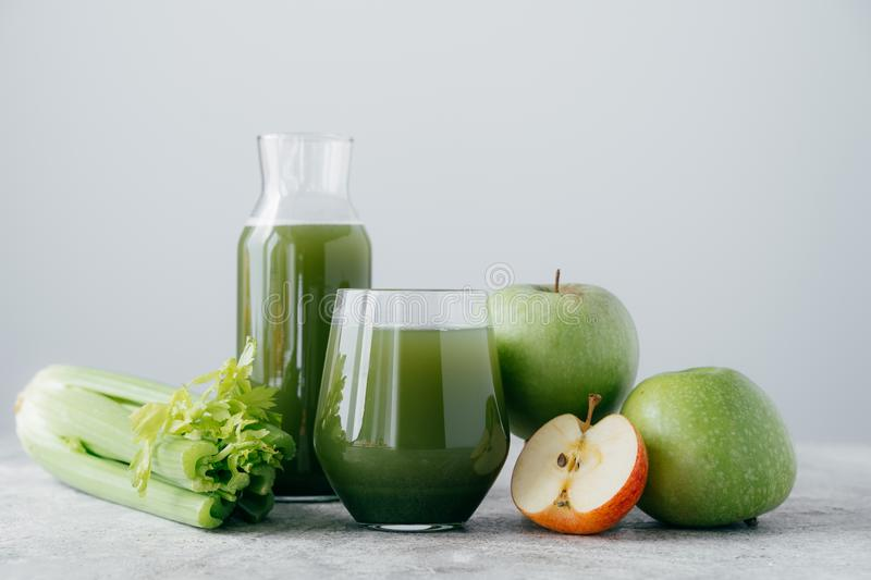 Horizontal shot of freshly blended apples and cerely for your healthy eating. Vegetarian green drink in glasses. Detox beverage, stock images