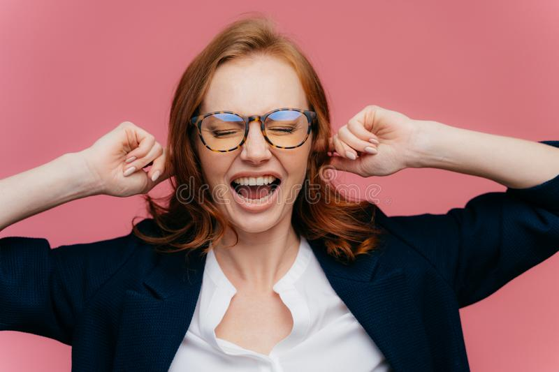 Horizontal shot of ginger woman in formal clothing, demonstrates gesture of ignore, plugs ears, shouts loudly, wears transprent. Glasses for vision correction royalty free stock image