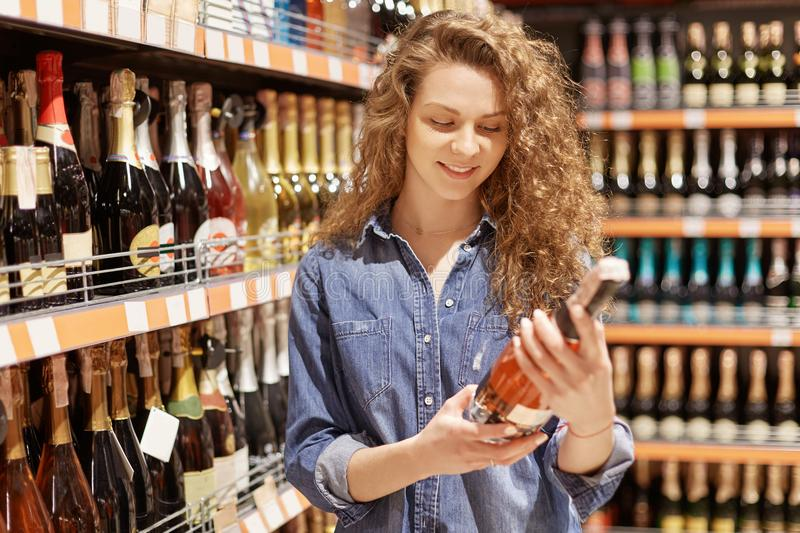 Horizontal shot of gorgeous attractive female with curly hair chooses alcoholic drink for party, reads label, wants something swee royalty free stock photo