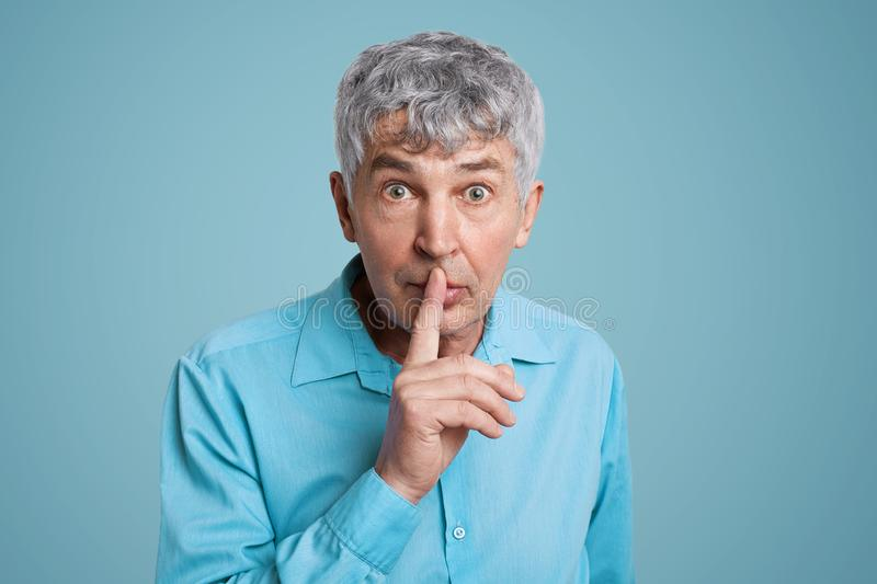 Horizontal shot of grey haired male looks with puzzled expression at camera, keeps fore finger on lips, asks to be quiet and mute,. Demands hush, dressed in royalty free stock images