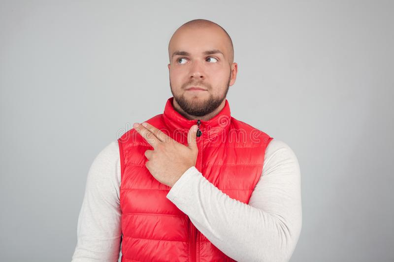 Horizontal shot of handsome bearded male with bald head, dressed in casual red waistcoat, looks curiously asdie, points with index stock photo