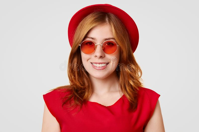 Horizontal shot of happy European female with sincere smile, wears everything in red colour, has fashionable style, glad after mak stock photography