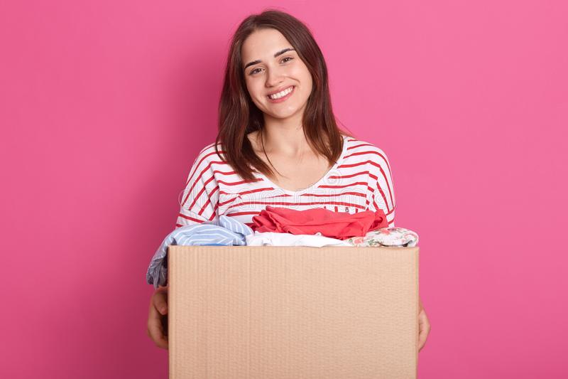 Horizontal shot of happy female posing isolated over pink background, holding carton box with rausable clothes, clothing for poor royalty free stock photo