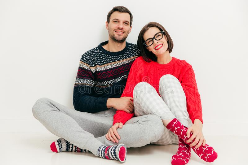 Horizontal shot of happy lovers sit together against white studio background, wear casual clothes, enjoy leisure time at home. Ad stock photography