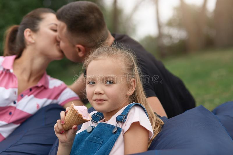 Horizontal shot of happy mother and father kissing while sitting on frameless chair in park with little daughter, cute blonde kid royalty free stock photography