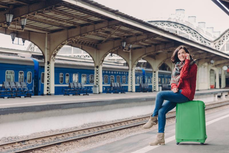 Horizontal shot of happy woman has telephone conversation, has spare time, sits at green bag, poses against railway station with royalty free stock photography
