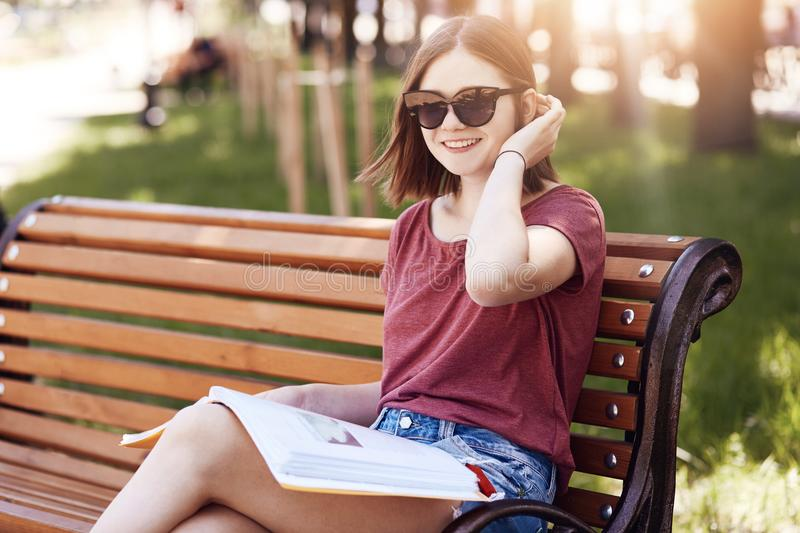 Horizontal shot of happy young female student wear shades and t shirt, reads maagzine on bench in park, has positive smile, poses royalty free stock photos