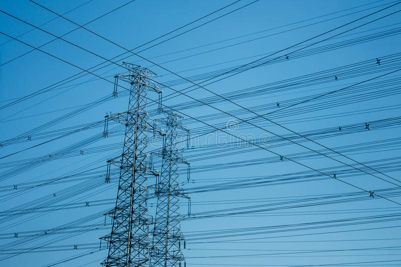 Horizontal shot of High-voltage towers silhouetted against blue royalty free stock photos