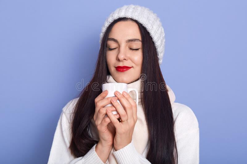 Horizontal shot of inspired delighted young lady closing eyes, holding white cup with hot drink, enjoying smell, being satisfied, stock photos