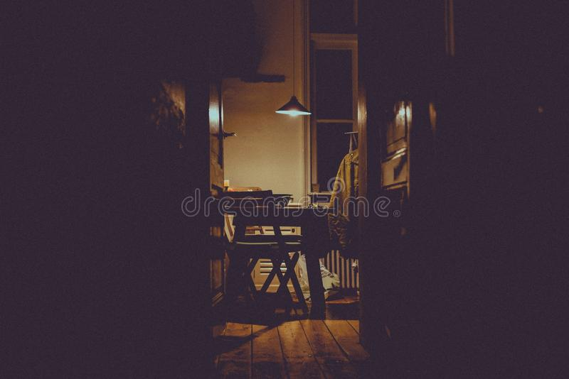 Horizontal shot of a kitchen`s interior with a table, two chairs, and a turned-on pendant lamp. A horizontal shot of a kitchen`s interior with a table, two royalty free stock photography