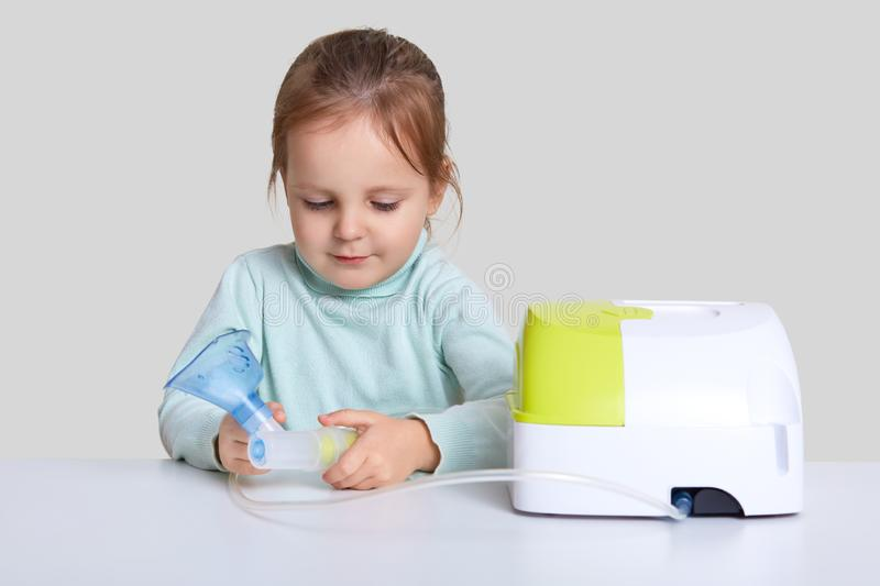 Horizontal shot of little girl sits at white desk with nebulous machine for health care, holds mask for making inhalation or stock image