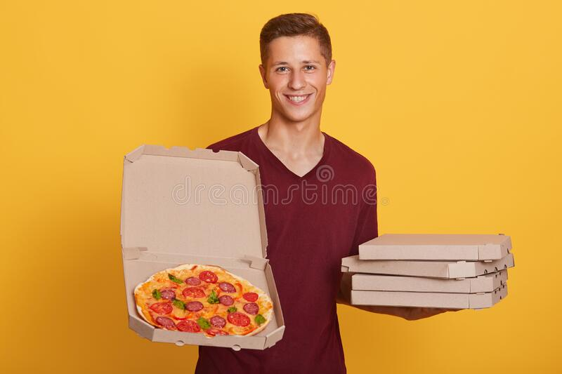 Horizontal shot of male holding picking tasty pizza, posing isolated over bright yellow studio background, attractive man wdresses stock photography