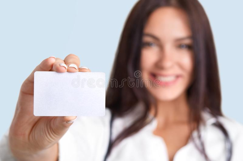 Horizontal shot of medical worker holds blank card, blurred silhouette, free space for your name and surname. Cute female nurse ho stock image