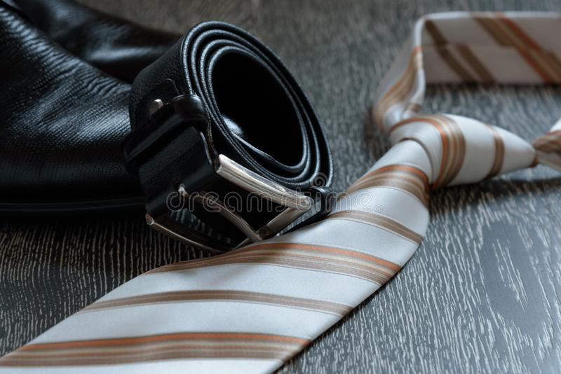 Men`s accessory set black boots, leather belt and tie on grey wooden background. royalty free stock images