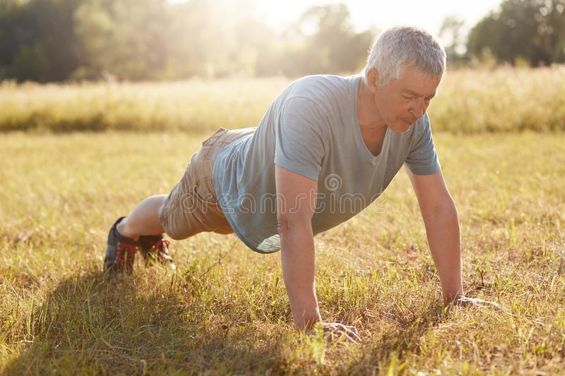 Horizontal shot of motivated mature sportsman makes plank on green grass, wears casual t shirt, shorts, sportshoes has workout on royalty free stock photos