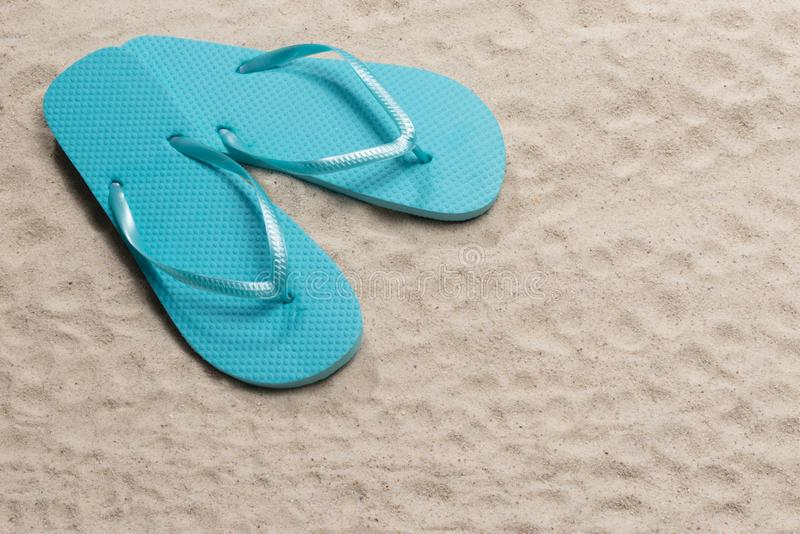 Blue Flip Flops on Beach Sand With Copy Space royalty free stock photography