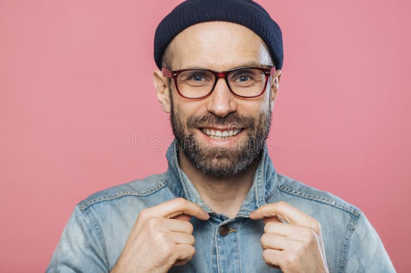 Horizontal shot of pleasant looking smiling bearded male wears glasses and denim jacket, advertizes new fashionable clothes, has h royalty free stock photography