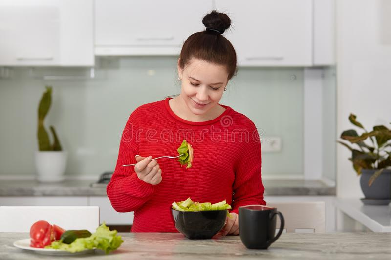 Horizontal shot of pleased pregnant woman enjoys tasty fresh salad from vegetables, drinks tea, wears casual clothes, poses. Against kitchen interior, has royalty free stock image