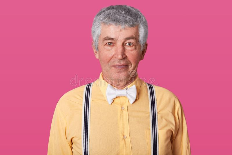 Horizontal shot of possitive grey haired mature man with wrinkled skin, dressed in yellow shirt in one tone, suspenders and white. Bow tie isolated over pink stock image
