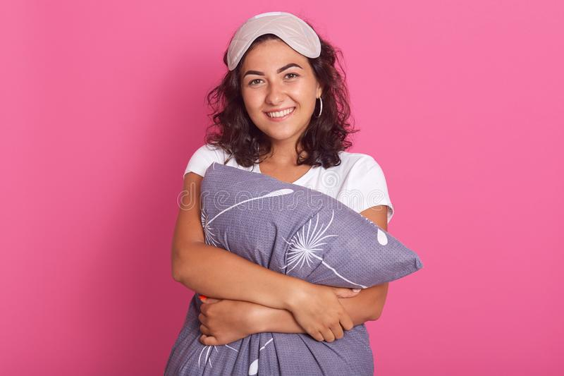 Horizontal shot of pretty relaxed sensual happy young woman hugging gray pillow, model posing over pink background, winsome dark stock photos