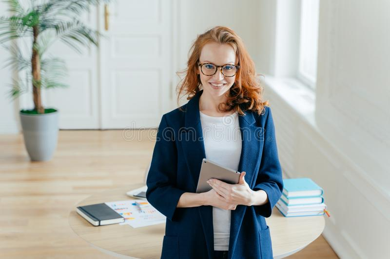 Horizontal shot of proud CEO checks email on digital touchpad, looks at camera with satisfied expression, wears spectacles, stands stock photography