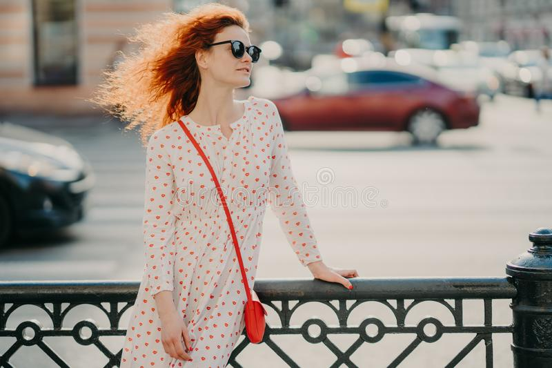 Horizontal shot of red haired woman wears sunglasses, focused aside, poses near hence at street, poses against road with transport royalty free stock images