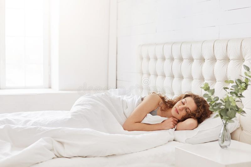Horizontal shot of relaxed carefree female under white bedclothes in bed at bedroom, sees pleasant dreams, keeps eyes. Closed, enjoys good rest at home and calm stock photos